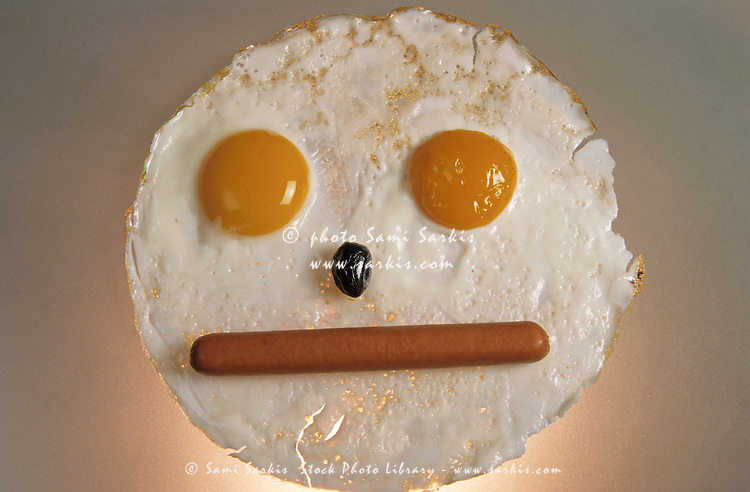 Fried breakfast of eggs and sausage made into a neutral face.