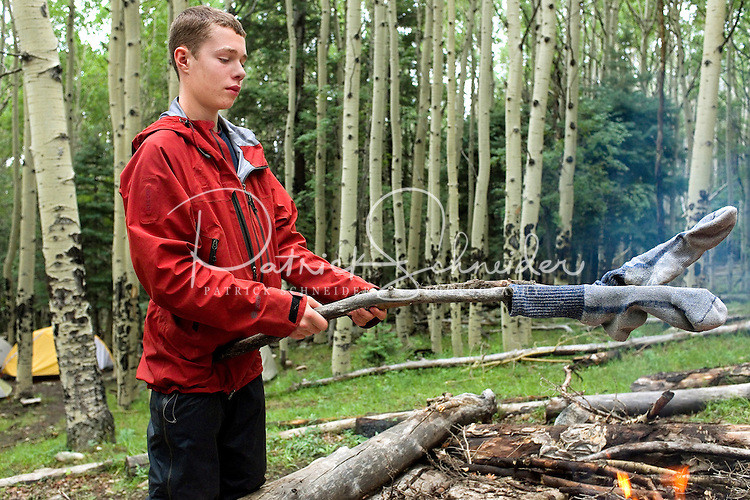 Photo story of Philmont Scout Ranch in Cimarron, New Mexico, taken during a Boy Scout Troop backpack trip in the summer of 2013. Photo is part of a comprehensive picture package which shows in-depth photography of a BSA Ventures crew on a trek.  In this photo BSA Venture Crew scout works to dry out his hiking socks with the campfire,  after heavy rains passed through the campsite in Baldy Town.<br /> <br /> The  Photo by travel photograph: PatrickschneiderPhoto.com