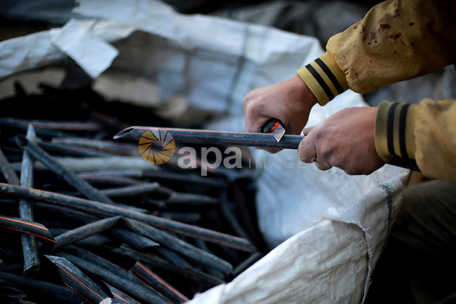 A Palestinian worker reuses plastics and metals to produce water hoses at a factory, in Gaza city, February 22, 2017. Workers collect the household recyclables, metals and plastic from landfill and garbage to sell to the local factories. Photo by Mohammed Asad