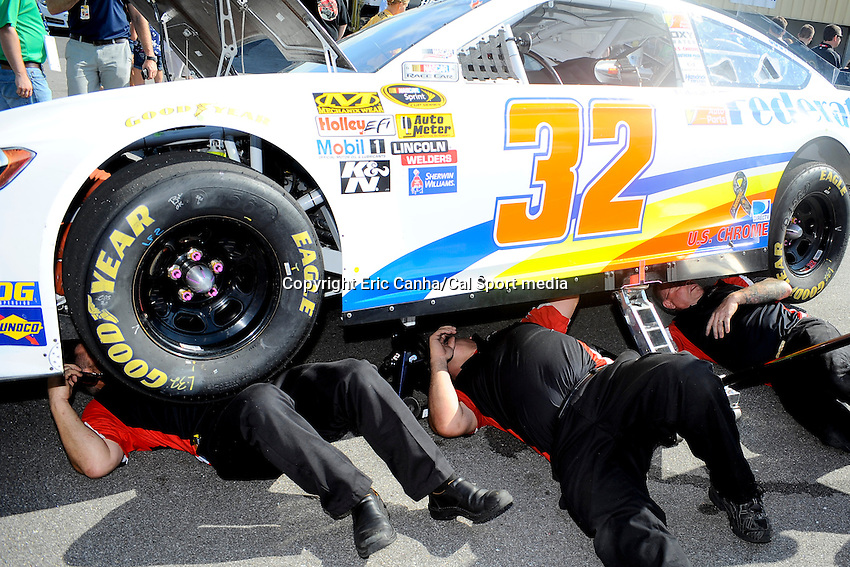 July 14, 2013 - Loudon, New Hampshire U.S. - Members of Sprint Cup Series driver Ken Schrader look for damage under the car. The #32 car's left wheel rolled off the edge of a ramp leaving the inspection area before the NASCAR Sprint Cup Series Camping World RV Sales 301 held at the New Hampshire Motor Speedway in Loudon, New Hampshire.   Eric Canha/CSM
