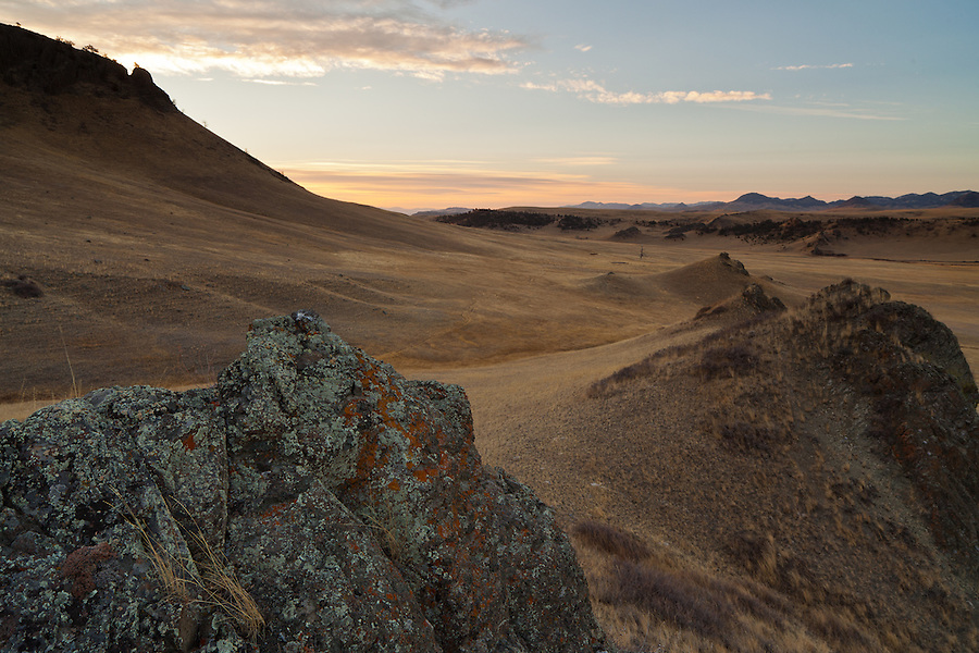The sun rises behind Crown Butte in Central Montana (Cascade County), casting a warm light over the prairie as seen from a rock outcropping.