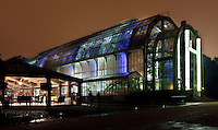 Tropical Rainforest Glasshouse (formerly Le Jardin d'Hiver or Winter Gardens), 1936, Rene Berger, with the  Desert and Arid Lands Glasshouse, 1930s, alongside, Jardin des Plantes, Museum National d'Histoire Naturelle, Paris, France. Low angle view of the illuminated glasshouses at night, showing the main Art Deco style entrance with its pillars in luminescent glass paste by Auguste Labouret in grand style. To the left is a cafe in glasshouse style.