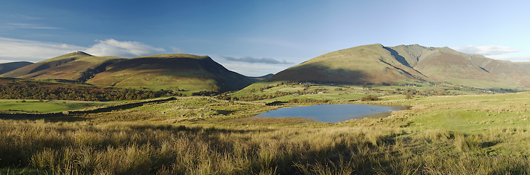 Tewet Tarn in the evening light looking towards Skiddaw and Blencathra, Lake District, Cumbria, Uk