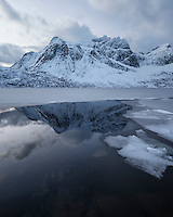 Stjerntind mountain peak rises above partially frozen water of lake Storvatnet, Flakstadøy, Lofoten Islands, Norway
