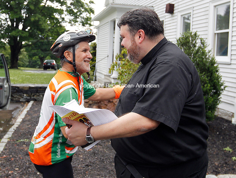 "Middlebury, CT-25 June 2012-062512CM01-  Lou Terzo (left) of Manchester is welcomed by Father Dennis Vincenzo (right) of St. John of the Cross Parish Monday afternoon in Middlebury.  The ""Brake the Cycle"" team, a group of men and women who cycle for a week each summer to raise awareness for poverty issues, stopped by the parish house during the journey.  Father Vincenzo opened up the house for the team to stay.     Christopher Massa Republican-American"
