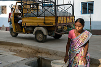 A woman fills up the bucket of municipal water while a delivery vehicle supplies bottled water to the local residents in Ambedkar Nagar in Medak, Telangana, India.