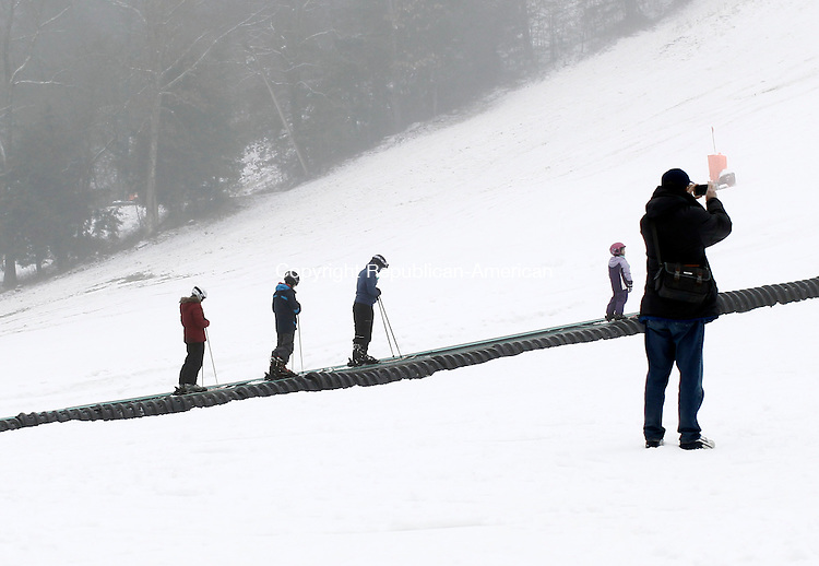 Woodbury, CT- 05 January 2015-010415CM07- A man takes a photo while skiers are transported up a hill at Woodbury Ski Area on Sunday.  Christopher Massa Republican-American