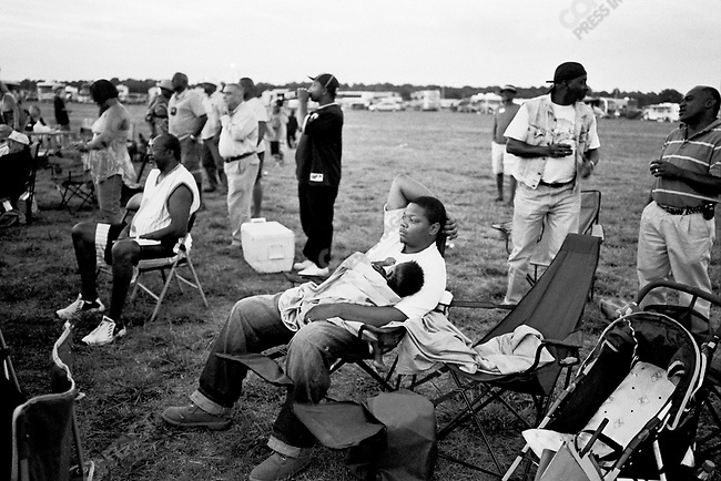 A father with sleeping child relax to the blues at the Greenville Blues Festival in Greenville, Mississippi, USA, September 2007