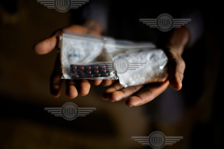 A man holding drugs given as part of palliative care in rural Malawi. Pioneering work with palliative care in rural Malawi is increasing the quality of life for thousands of people with terminal conditions including cancer, TB and arthritis-often linked to HIV infection which remains at around 10 percent of the adult population.