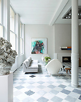 In the living room, the ceiling is lined with fir planks that have been primed and the floor is tiled with antique marble. The room is furnished with unique pieces spanning several decades such as the 1970s sofa by Harvey Probber, covered in an Old World Weavers wool and as the 1950s armchairs by Joseph-André Motte, upholstered in a Holland & Sherry fabric. Among the many artworks displayed in the room are a painting by George Condo, a sculpture by Rebecca Warren and a wall sculpture by Donald Judd above the Thassos marble fireplace.