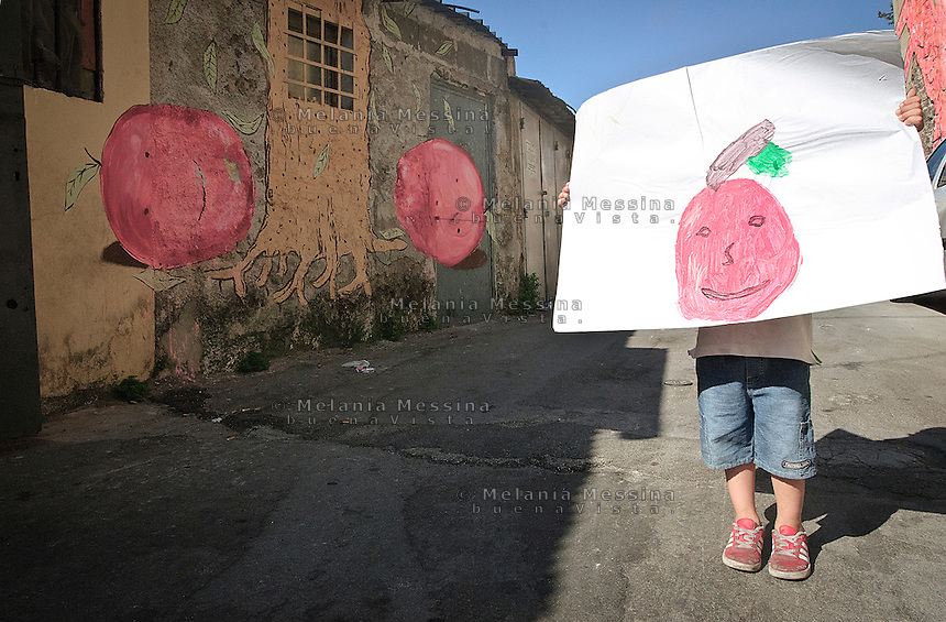 Palermo, quartiere Borgo vecchio, periferia degradata nel cuore della citt&agrave;.un bambino mostra il disegno che ha ispirato il murales.<br />