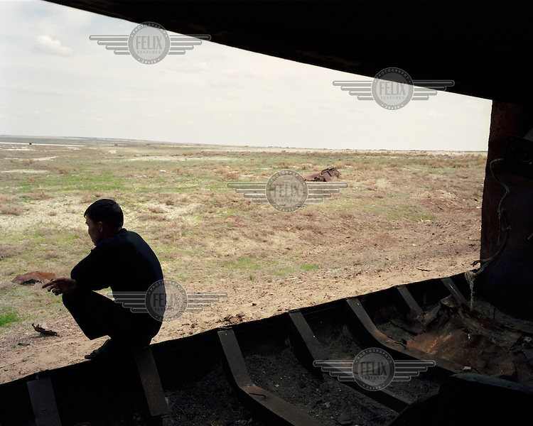 A local fixer sits on the edge of a rusting ship, in an area which used to be covered with water before the Aral Sea was drained during Soviet rule. He has been asked to find alternative locations by the film crew who employ him as the iconic ship carcasses that once populated this area have all but disappeared.