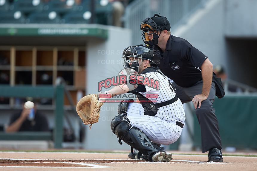 Charlotte Knights catcher Brett Austin (22) catches a pitch as home plate umpire Brian Peterson looks on during the game against the Indianapolis Indians at BB&T BallPark on May 26, 2018 in Charlotte, North Carolina. The Indians defeated the Knights 6-2.  (Brian Westerholt/Four Seam Images)