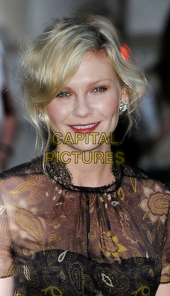 Kirsten Dunst (wearing new fashion label Honor's spring 2012 collection).UK Premiere of 'Melancholia' at the Curzon, Mayfair, London, England..September 28th 2011.headshot portrait organza paisley printed gold woven weave sheer black brown pink lipstick .CAP/WIZ.© Wizard/Capital Pictures.