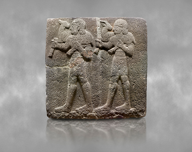 Hittite monumental relief sculpted orthostat stone panel of a Procession Basalt, Karkamıs, (Kargamıs), Carchemish (Karkemish), 900-700 B.C.  Anatolian Civilisations Museum, Ankara, Turkey. Young male servants of Kubaba while carrying sacrificial animals on their shoulders. <br /> <br /> Against a grey art background.
