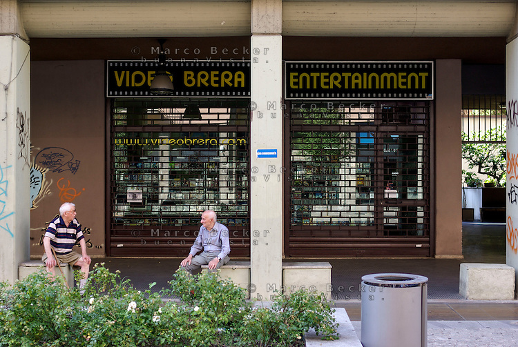 Milano, due anziani discorrono seduti sotto ai portici di corso Garibaldi, con dietro un negozio videoteca noleggio video chiuso per ferie --- Milan, two old men sitting under the arcade in Garibaldi street and talking, with a video store closed for vacation behind them