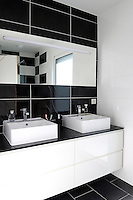 This bathroom with double wash basins has a retro decorative theme with its large black and white ceramic tiles
