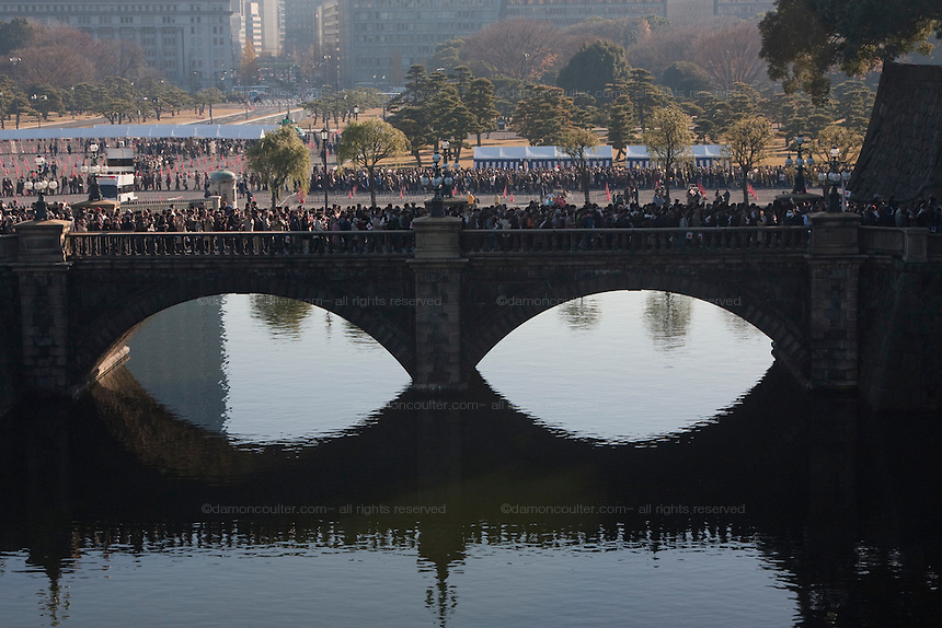 """Police control well-wishers as they  cross the """"Spectacles Bridge""""  a double arch bridge to enter the Imperial Palace. Emperor Akihito 76th birthday was celebrated in Japan with a national holiday and thousands of well-wishers being allowed into the Royal Palace for the occasion. He made three appearances during the day and spoke of the economy difficulties many Japanese people are suffering during his address. He was accompanied by Empress Michiko, Crown Prince Naruhito, Prince Akishino and their wives. Tokyo, Japan December 23rd 2009"""