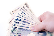 A close up of Japanese 1,000 and 10,000 banknotes with intentional selective focus.