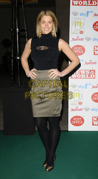 GEMMA ATKINSON.Children's Champions Awards 2009 at the Grosvenor House Hotel, Park Lane, London, England..March 4th 2009.full length black sleeveless polo neck top tucked in high waisted khaki green skirt tights leopard print shoes Christian Louboutin heels gold hands on hips belt.CAP/CAN.©Can Nguyen/Capital Pictures.