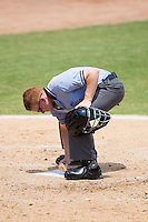 Home plate umpire R.J. Dyett cleans off home plate during the Carolina League game between the Frederick Keys and the Winston-Salem Dash at BB&T Ballpark on July 30, 2014 in Winston-Salem, North Carolina.  The Dash defeated the Keys 12-2.   (Brian Westerholt/Four Seam Images)