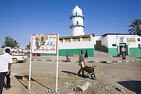 "Djibouti. Djibouti province. Djibouti. Mosque with a minaret. Black muslim people walk on the road. The sign in arabic language says: "" The poor and the needy persons will be happy with your zakat. (The zakat is an obligatory duty, the third of the five pillars of islam, and refers to spending a fixed portion of one's wealth for the poor ot the needy. )  © 2006 Didier Ruef"