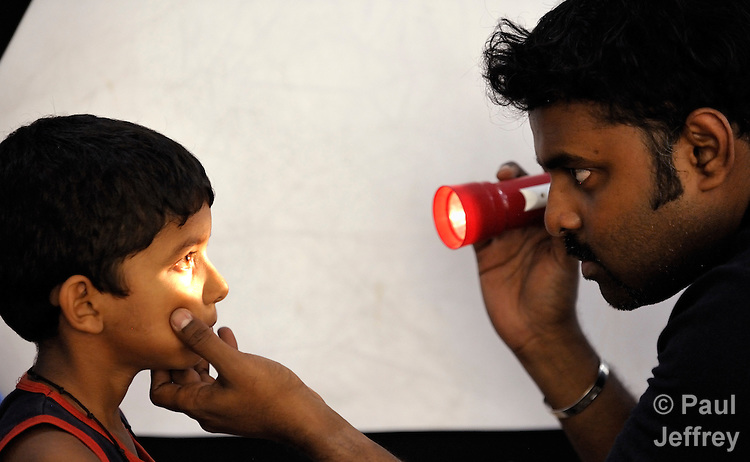 Dr. Muraganantham (right) examines a young patient at an eye clinic for the poor in Chennai, a city in the southern India state of Tamil Nadu.