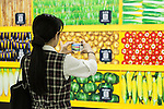 A woman takes a picture of a massive 80 meter ''Wall Farmer's Market'' information poster in the Tokyo Metro passageway in Shinjuku on September 1, 2015, Tokyo, Japan. The Central Union of Agricultural Co-operatives (JA-ZENCHU) is promoting Japanese vegetables with the vegetable columns and a massive 80 meter information poster until September 6th. (Photo by Rodrigo Reyes Marin/AFLO)
