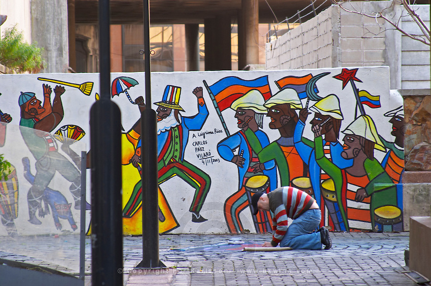A man making a street painting on the pavement in front of a wall fresco painting with colourful men depicting an historic event titled A Lagrima Rios by Carlos Paez Vilaro Montevideo, Uruguay, South America