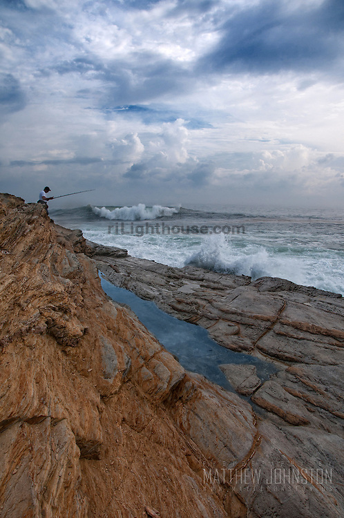 A man fishes on the rocky coast of Beavertail as waves crash nearby.