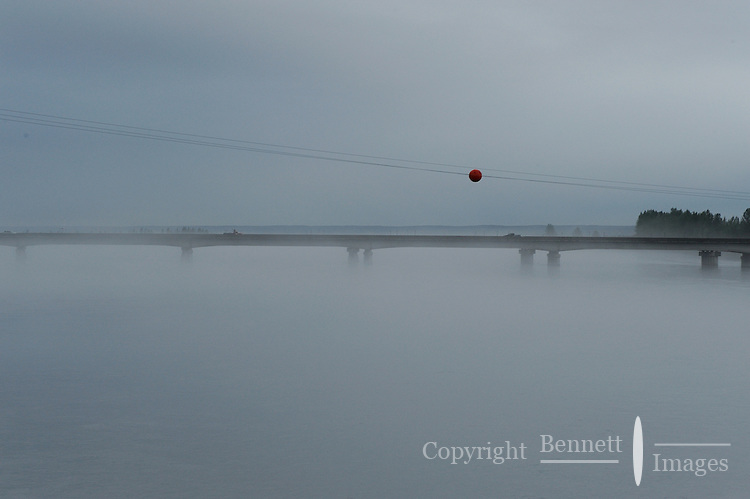 A powerline and the Glenn Highway bridge over the Knik River emerge from the mist on a foggy morning. The Alaska Railroad's Denali Star train runs between Anchorage and Fairbanks, with Denali one of the stops along the way.