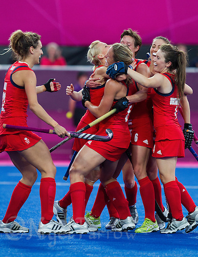 02 AUG 2012 - LONDON, GBR - Crista Cullen (GBR) (centre facing left with dark hair) of Great Britain celebrates scoring Great Britain's third goal of the teams 3-0 win against Belgium with Alex Danson (GBR) (left)  during their London 2012 Olympic Games preliminary round hockey match at the Riverbank Arena in the Olympic Park at Stratford, Great Britain (PHOTO (C) 2012 NIGEL FARROW)