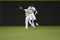 Columbia Fireflies outfielders Zach Rheams (23), Edgardo Fermin (10) and Jay Jabs (21) jump and bump to celebrate an 11-2 win over the Charleston RiverDogs on Tuesday, August 28, 2018, at Spirit Communications Park in Columbia, South Carolina. (Tom Priddy/Four Seam Images)