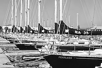 "US Naval Academy 44 foot sail training craft (Navy 44s) including ""Fearless"", ""Valiant"", and ""Audacious"" sit at anchor in Santee Basin at the USNA Sailing Center awaiting their next training mission.  The US Naval Academy is located in Annapolis, Maryland."