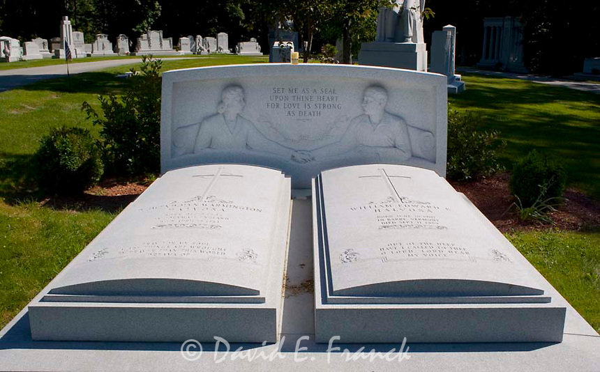 Couple holding hands in twin beds gravestones at the Hope Cemetery in Barre, Vermont the granite capital of the world.
