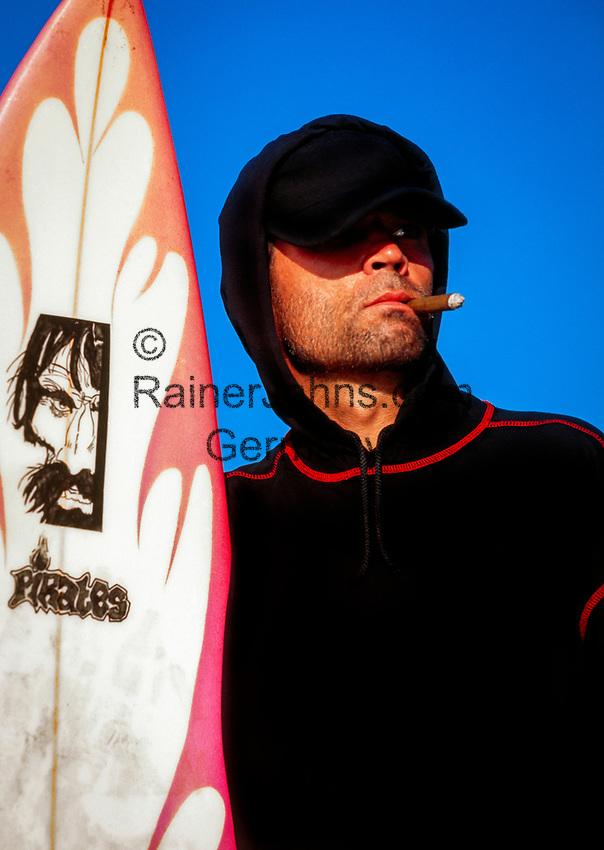 Spanien, Kanarische Inseln, Fuerteventura, junger Mann mit Kapuzenshirt raucht Zigarre, haelt Surfboard im Arm | Spain, Canary Island, Fuerteventura, young man with hoody, smoking cigar, holding surfboard in arms