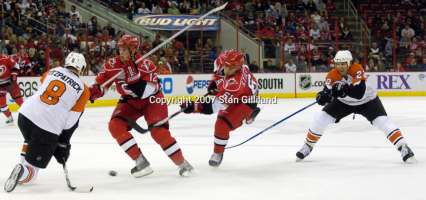 The Carolina Hurricanes' Cory Stillman fires a shot defended by the Philadelphia Flyers' Rory Fitzpatrick (8) and Michael Knuble (22) as teammate Eric Staal helps Wednesday, Nov. 21, 2007 in Raleigh, NC. The Flyers won 6-3.