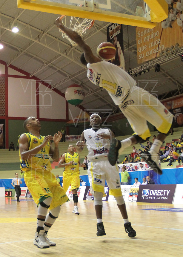 BBUCARAMANGA -COLOMBIA, 11-06-2013. Gilbert Lawrence (Arriba) de Búcaros realiza una clavada en contra de Bambuqueros durante el juego 4 de la final en la DirecTV de baloncesto Profesional de Colombia realizado en el Coliseo Vicente Díaz Romero de Bucaramanga./ Gilbert Lawrence (Up) of Bucaros makes the dunk against Bambuqueros during the game 4 of the final on DirecTV professional basketball League in Colombia at Vicente Diaz Romero coliseum in Bucaramanga. Photo: VizzorImage / Jaime Moreno / STR