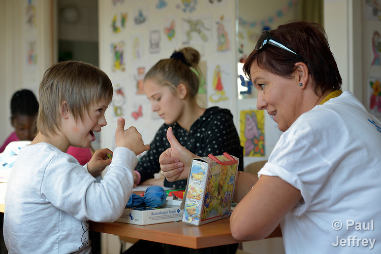 Vullnet Gashi (left), a 10-year old refugee from Kosovo, interacts with Gyöngyi Wingelmann, a staff member of Hungarian Interchurch Aid, in a government-run refugee center in Vamosszabadi, Hungary. Hungarian Interchurch Aid, a member of the ACT Alliance, provides child care and other services to residents in the center, who come from Syria, Iraq and other countries and are bound for western Europe.