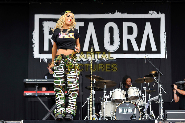 Rita Ora.performing at the Barclaycard Wireless Festival, Hyde Park, London, England. 7th July 2012..music live gig on stage show full length microphone black beanie hat crop top t-shirt  cropped midriff  slogan writing army green trousers camouflage  .CAP/MAR.© Martin Harris/Capital Pictures.