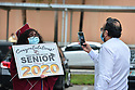 PEMBROKE PINES, FL - MAY 15: A parent takes a photo of a student in the parking lot at Pembroke Pines Charter High School on May 15, 2020 in Pembroke Pines, Florida. Because of social distancing mandates instituted by the state to curtail the spread of COVID-19, the 2020 graduates received their diplomas in a near-empty auditorium with no friends, family or relatives allowed to attend. A video of each student walking the stage to receive their diploma will be streamed on the school's scheduled graduation date of May 29.   ( Photo by Johnny Louis / jlnphotography.com )