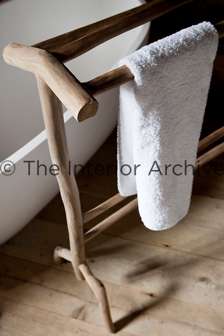 The free-standing contemporary bath tub is accessorised with a rustic wooden towel rack
