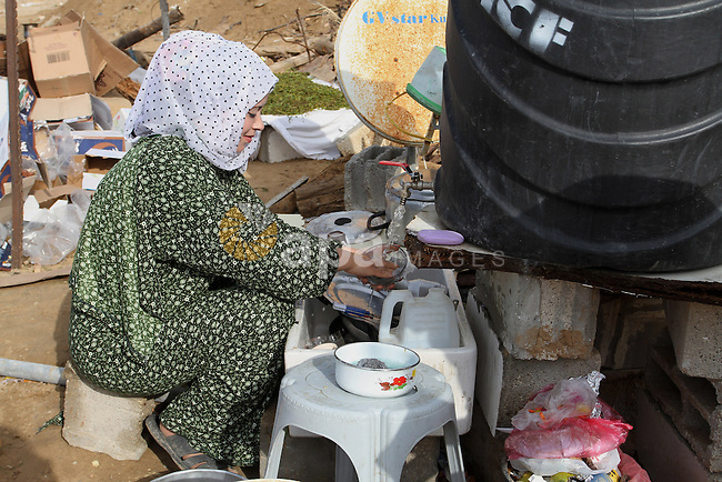 A Palestinian woman, whose house was destroyed by what witnesses said was Israel shelling during a 50-day conflict last summer, works outside her tent east of Khan Younis in the southern Gaza Strip January 27, 2015. The main U.N. aid agency in the Gaza Strip said on Tuesday a lack of international funding had forced it to suspend payments to tens of thousands of Palestinians for repairs to homes damaged in last summer's war. Robert Turner, Gaza director of operations for the United Nations Relief and Works Agency (UNRWA), said in a statement that UNRWA received only $135 million of the $720 million pledged by donors to its cash assistance program for 96,000 refugee families whose homes were damaged or destroyed in the 50-day conflict between the Hamas Islamist movement and Israel. Photo by Abed Rahim Khatib