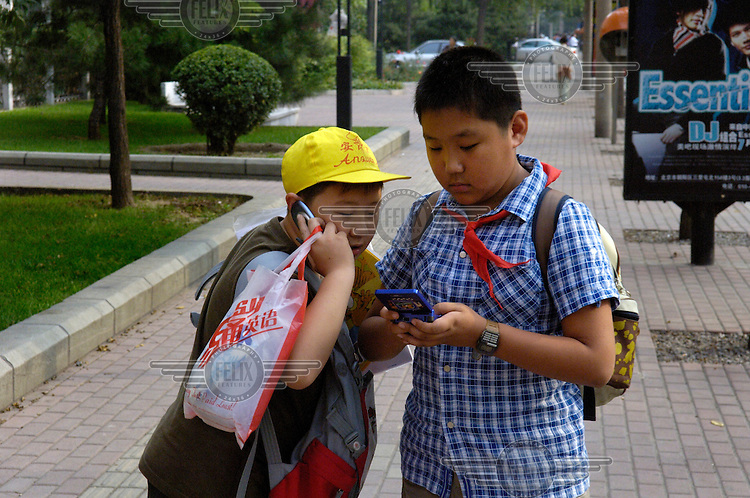 Lucky school children, one with a video game, the other talking on his mobile phone, just out of a city centre school. Spoilt children, the products of the country's draconian one-child policy, are known as 'Little Emperors'.