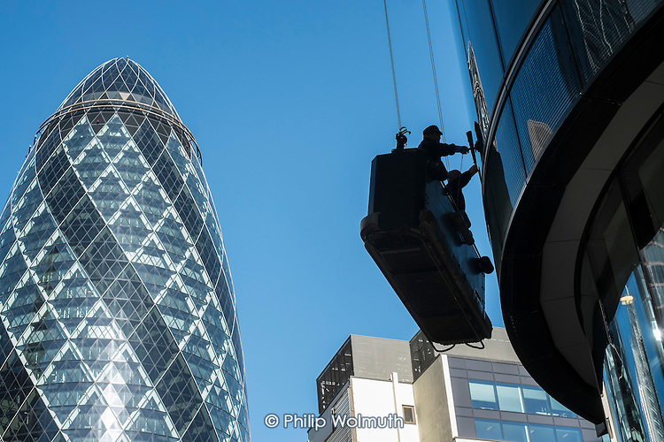 Window cleaners working from a cradle on a high-rise office block in the City of London close to 30 St. Mary Axe (The Gherkin).