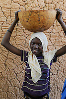 NIGER Zinder, young woman with calabass on the head in village BABAN TAPKI / NIGER Zinder, Dorf BABAN TAPKI, Caritas CADEV Projekte Ernaehrungssicherung, Familie von MARIAMA MOUSSA wird mit Nahrungsmitteln unterstuetzt