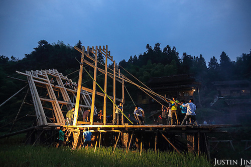 At the crack of dawn, friends and family gather to help pull up a house that has been stacked in a pile by the master engineers.