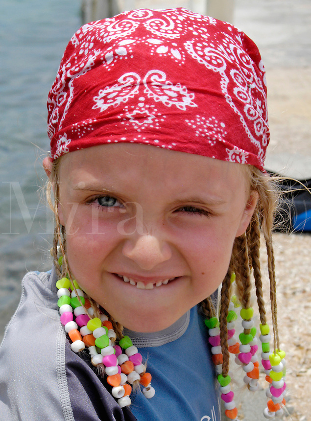 Young girl (MR) wearing a bandanna standing at the water's edge.