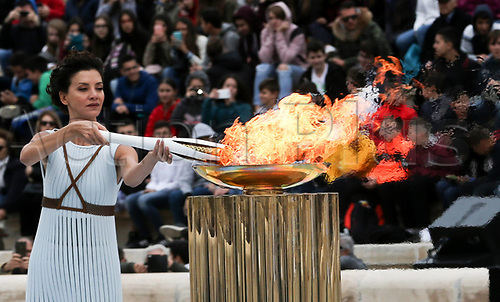 October 31st 2017, ATHENS, Greece;- Actress Katerina Lehou playing the role of high priestess lights an Olympic torch during the handover ceremony for the Olympic Flame at Panathenaic stadium in Athens, on Oct. 31, 2017, The Flame burning for the 2018 PyeongChang Winter Olympics was handed over on October 31st to the South Korean organizers