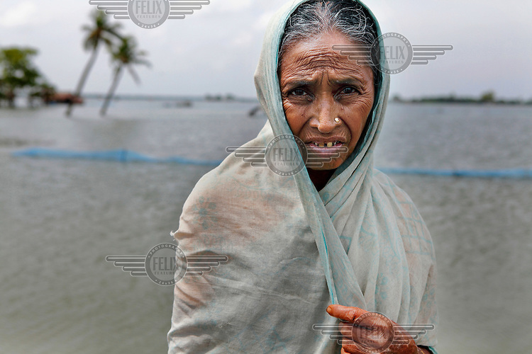 A woman stands in flood waters that have innundated the Satkhira District. Each year limited flooding helps to enrich the soil and create very fertile farm land. In turn, this results in a high population density on the flood plain. However, the low lying land is also prone to extreme flooding events that are very destructive to both the economy and human life.